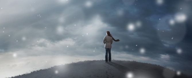 A woman standing on top of a hill in a snow storm