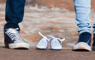 Two parents stand by empty small shoes