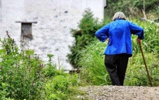 Stroke patient walks with can through garden