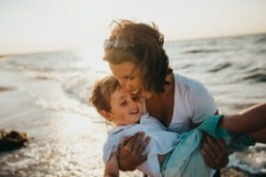 Woman with young son on beach demonstrates how happy you will feel after you get acupuncture for your jaw pain.